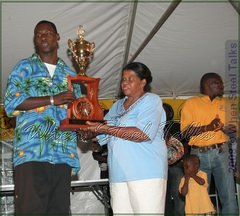 "Khan Cordice, arranger for the Antigua & Barbuda National Youth Pan Orchestra receives winning trophy from Mrs. Curlita Gordon, widow of Leroy ""Jughead"" Gordon"